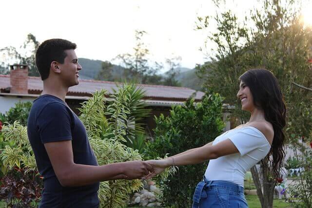 手を繋いで向かい合っている男性と女性
