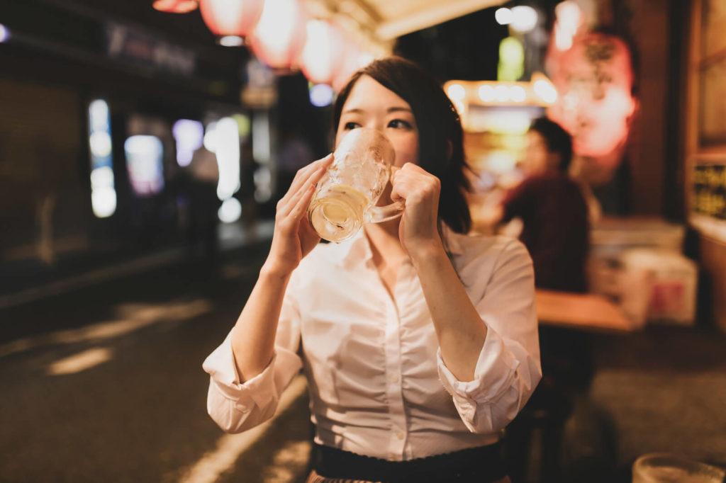 店の外でビールを飲む女性
