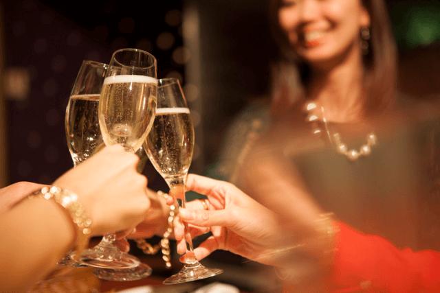 シャンパンを乾杯している女性とグラス