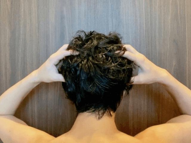 頭皮をマッサージしている上半身が裸の男性