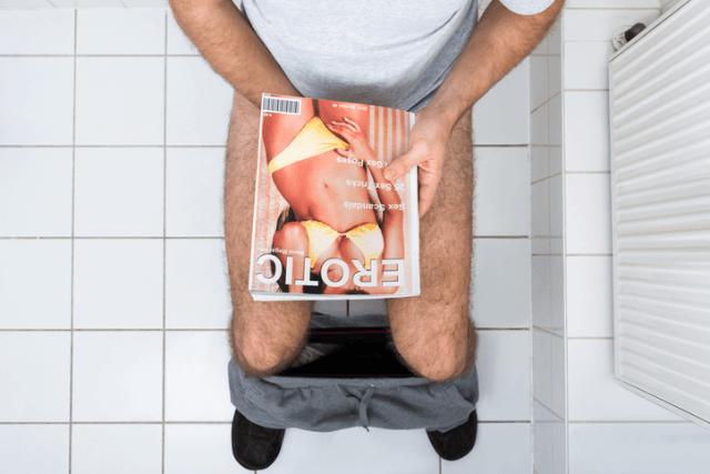 ズボンを脱ぎ雑誌で陰部を隠してトイレに座っている男性