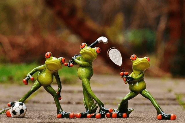 サッカーとゴルフとテニスをするカエルの置物