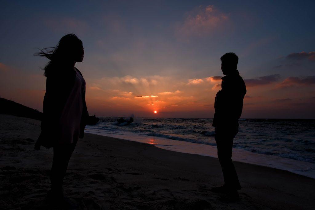 女性と男性が海辺で夕日を眺めている