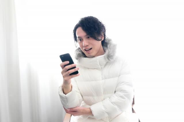 ロングジャケットを着てiPhoneを捜査している笑顔の男性