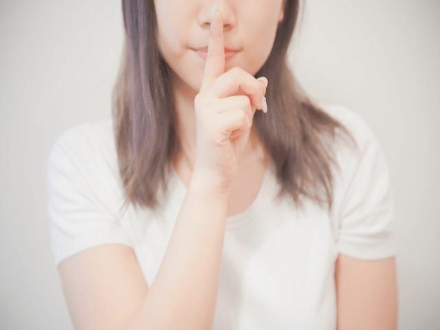 口元に人差し指を当てている女性