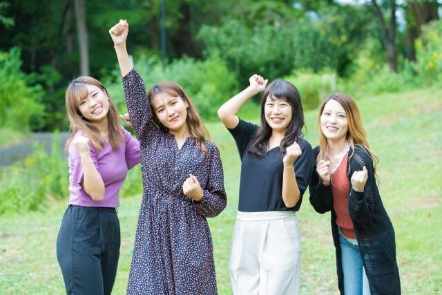 笑顔でこぶしを掲げている女性たち