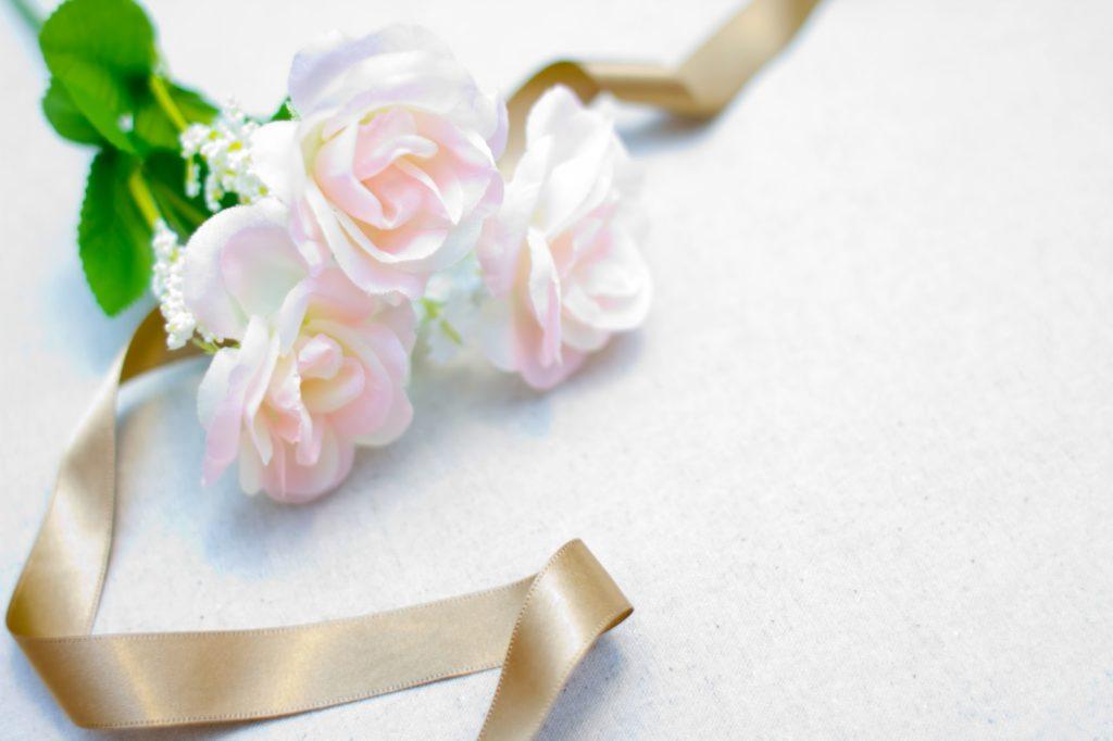 ゴールドのリボンを付けている薄ピンク色のバラ