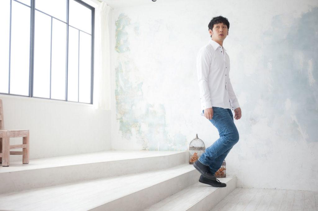 シャツとジーンズの姿で階段を降りている男性