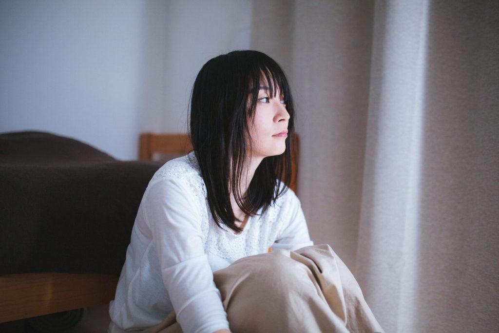 カーテンの閉じた暗い部屋で外を見ている寂し気な顔の女性