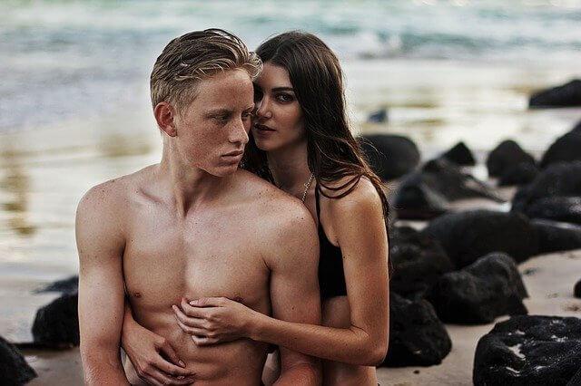 神妙な顔で後ろから男性に抱きついている裸の女性