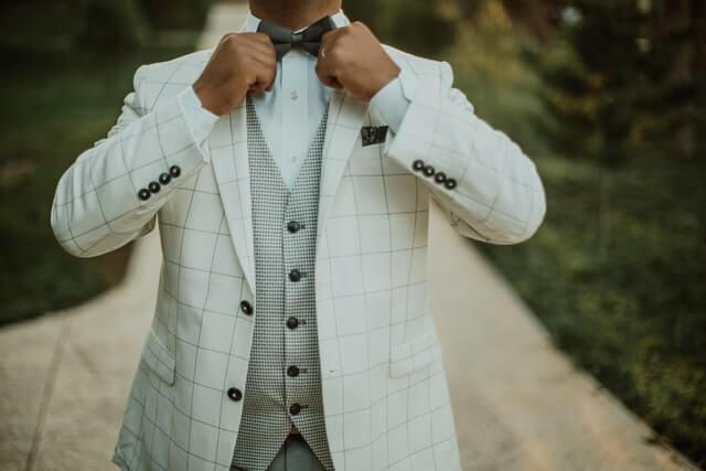 蝶ネクタイを整える男性