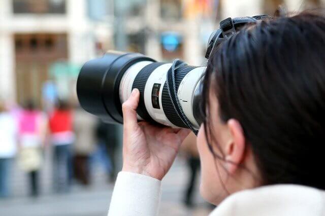 カメラで人込みを撮影している女性