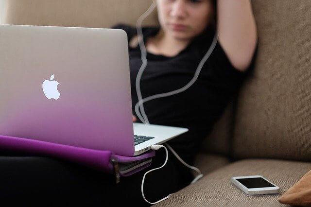 ソファで寛ぎながらパソコンとiPhoneを見ているイヤフォンをつけた女性