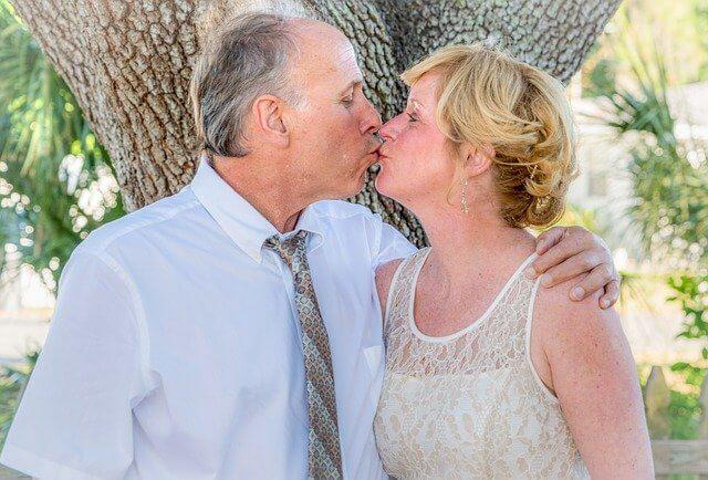 木の幹でキスをする年老いた夫婦