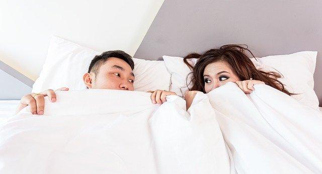口元まで布団をかぶり目を合わせているカップル