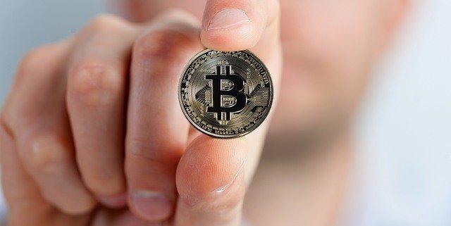 男性が人差し指と親指でコインを持っている