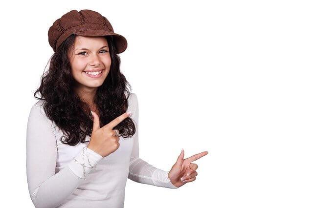 両手の親指と人差し指を横向きに差している笑顔の女性