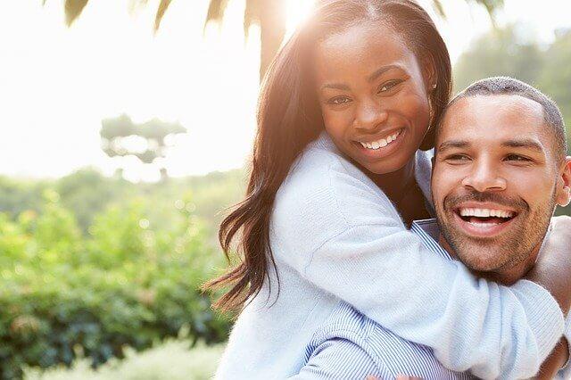 笑顔の女性をおんぶしている笑顔の男性