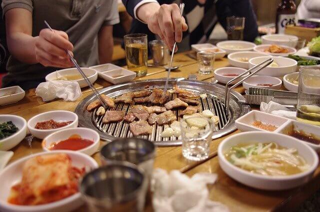焼肉とお箸で肉をとる男2人の手