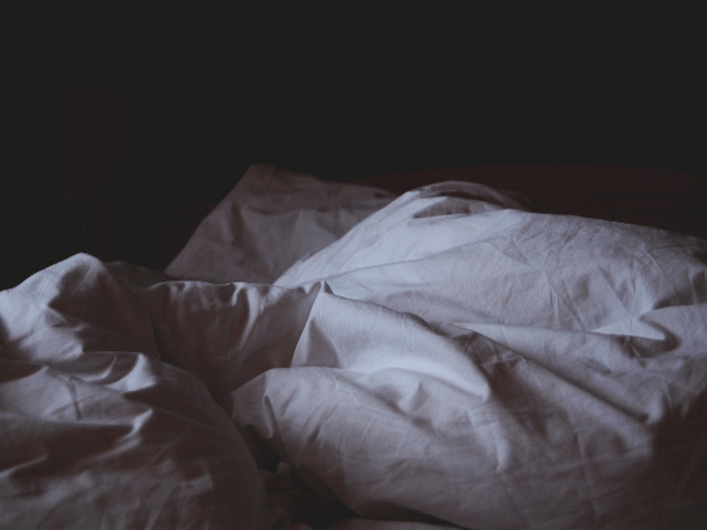 薄い部屋に置かれているベッド