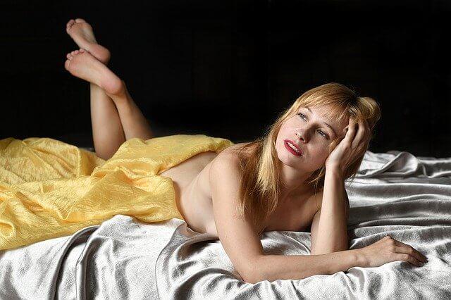 シーツを纏う裸でベッドに横たわる女性