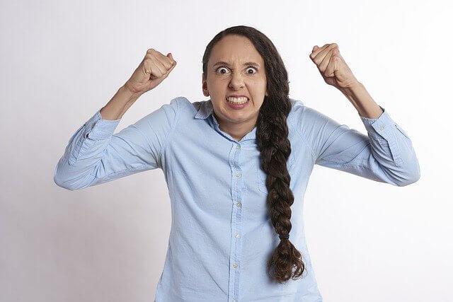 耳の横にこぶしを作って怒っている女性