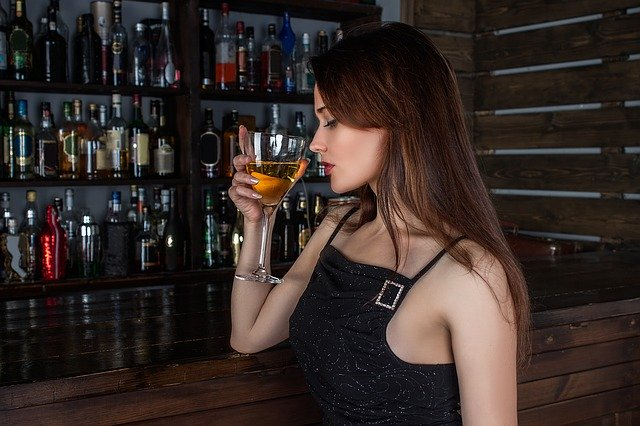 女性が立ってウイスキーのにおいを嗅いでいる