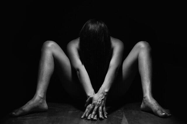 裸で下半身を隠して下を向いている女性