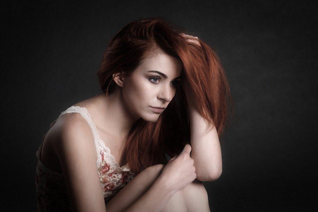 髪の毛を触り座っている女性