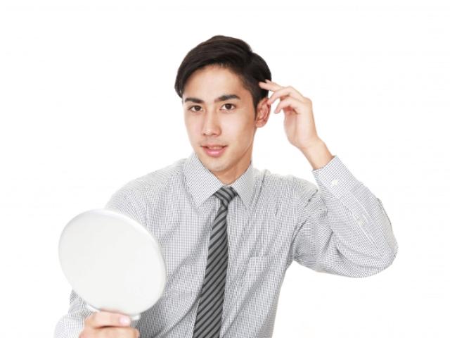 髪の毛を整えているスーツの男性