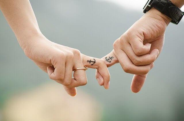 錨の刺青が彫られている男女の人差し指が絡まっている