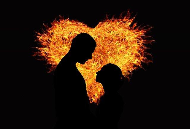 炎のハートを背に見つめあう男女の影