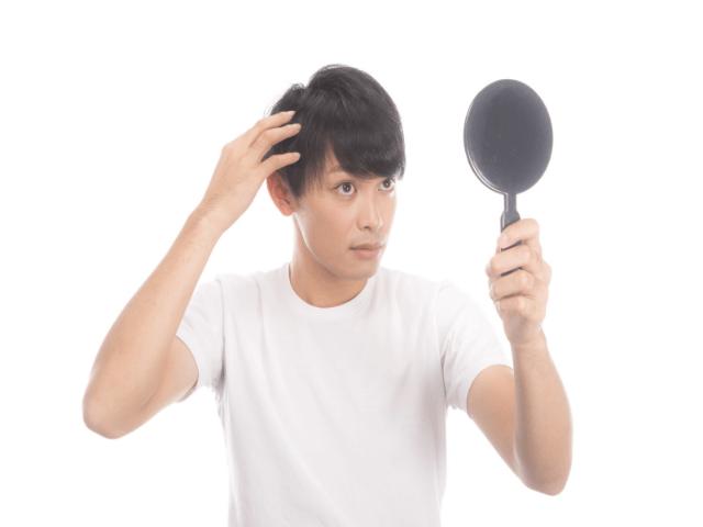 髪の毛を鏡で見ている男性