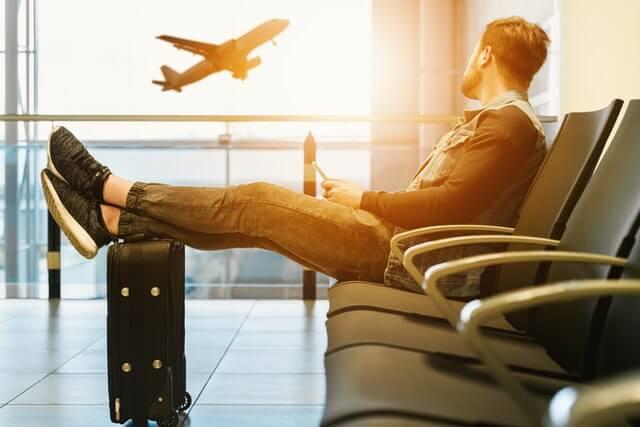 スーツケースに足を上げて座り、飛んでいる飛行機を眺める男性
