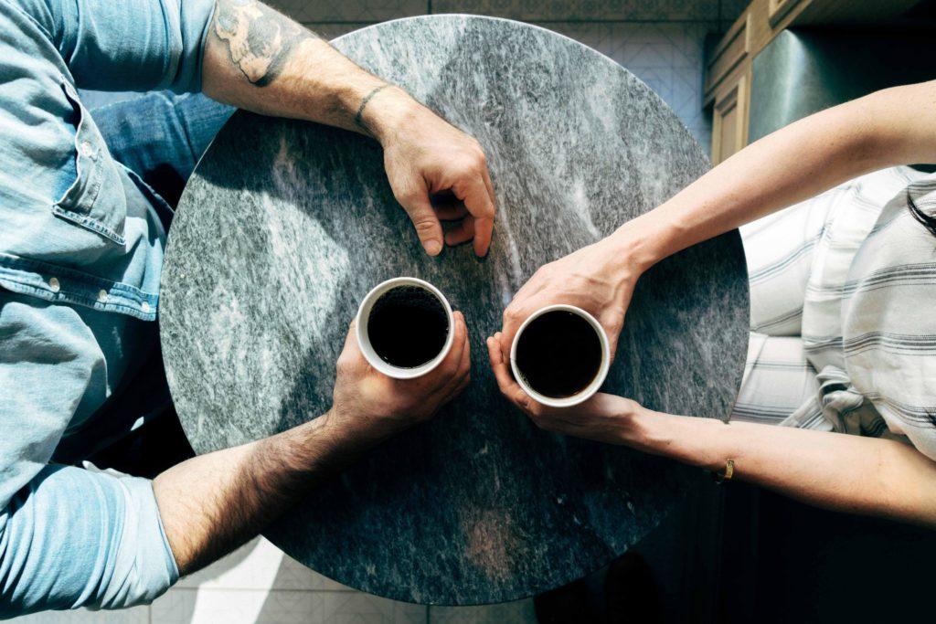 コーヒーを手に持っている男女