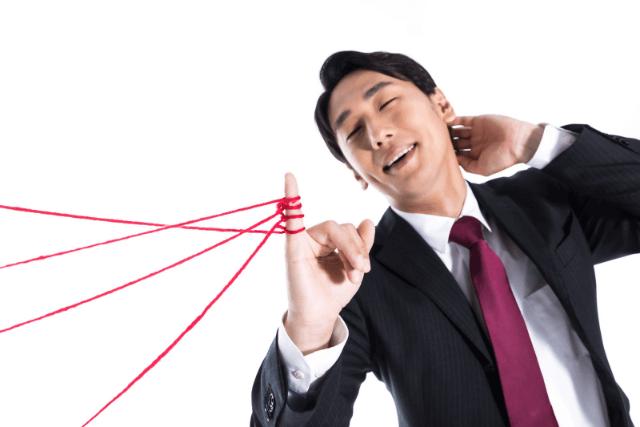 小指を赤い糸で繋がれているスーツ姿の男性