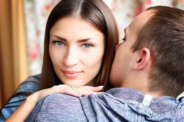 髪にキスをする男性の肩に顎を乗せる女性