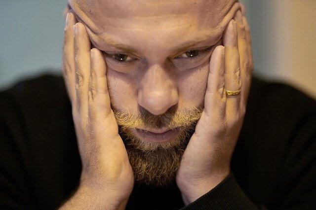 両手でこめみに手を当て悩んでいる顎髭の生えた男性