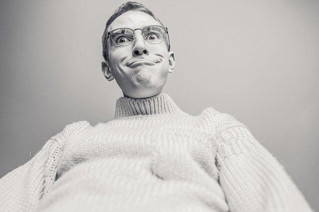 顎を突き出して上から見下ろすメガネの男性