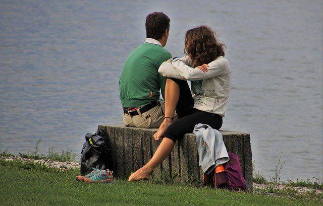 湖のイスに座って話している男女