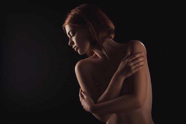 上半身裸で胸を隠している短髪の女性