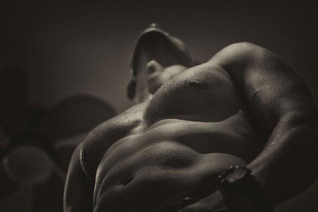 下半身を触って上を向きながら感じている裸の男性