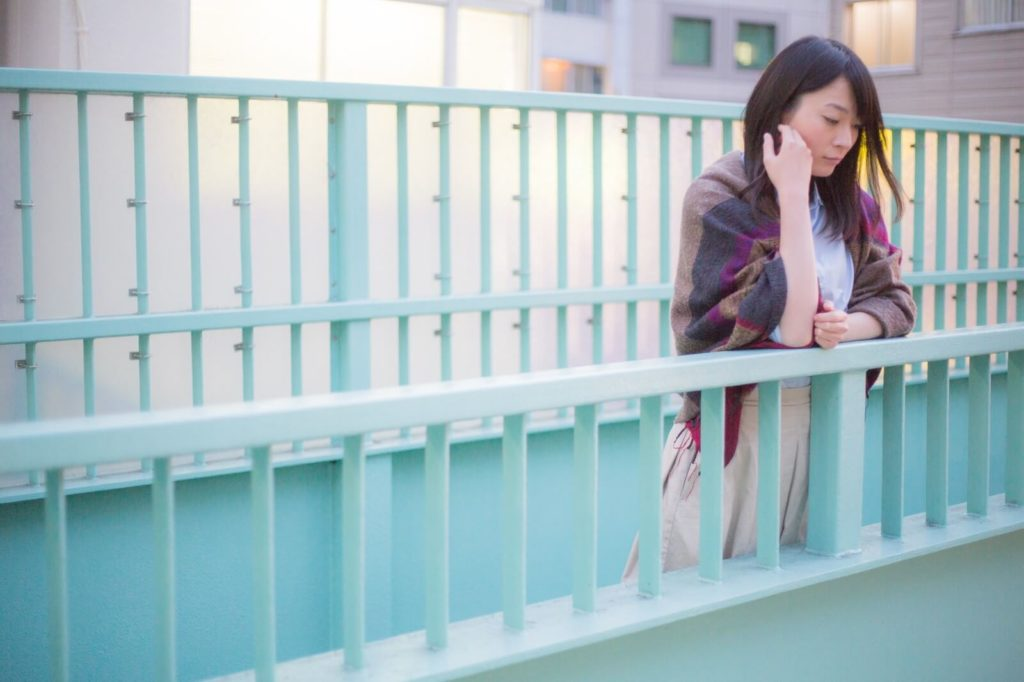 歩道橋から下を見下ろす物憂げな表情の女性