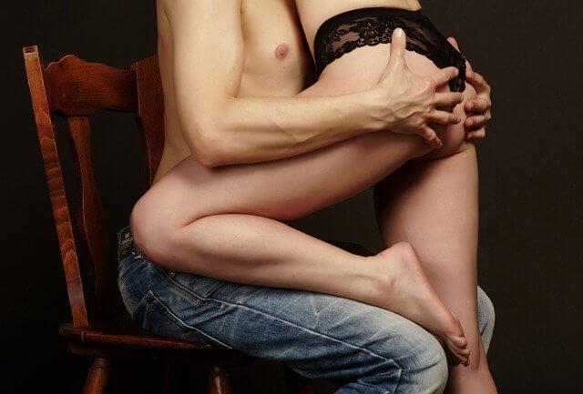 上半身裸の男性と下着姿の女性が抱き合っている