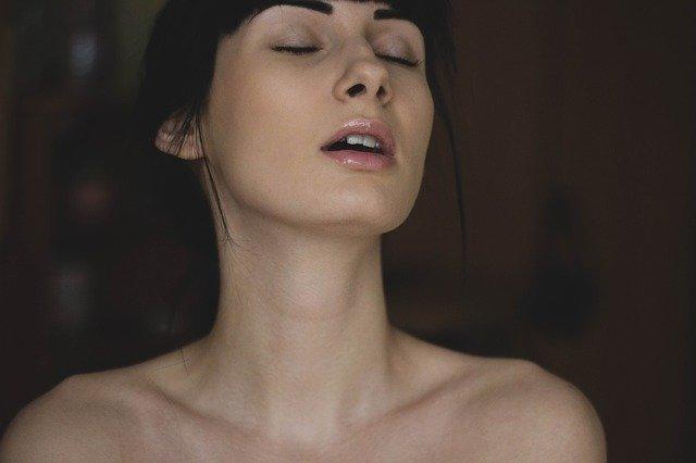 目をつむり口を少し開けて感じている裸の女性