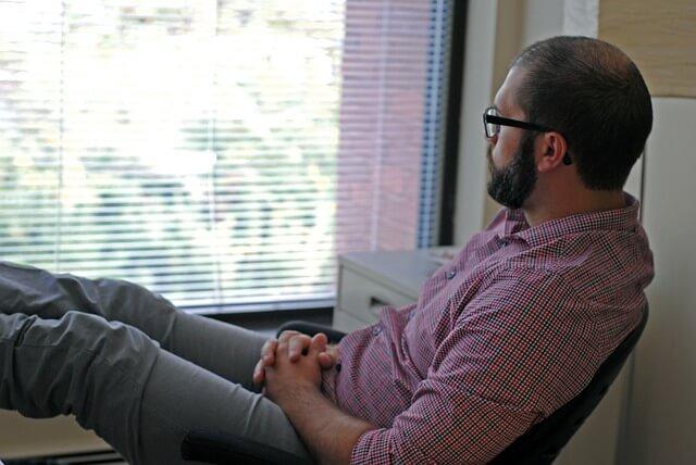 イスに座り外を眺めているチェックシャツにメガネをかけた男性