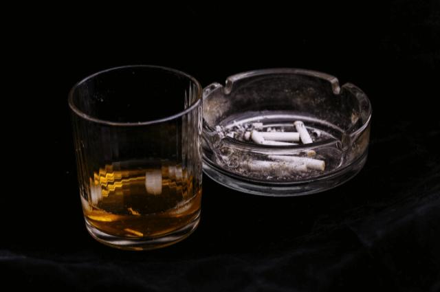 お酒が入ったグラスとタバコの吸殻が入った灰皿