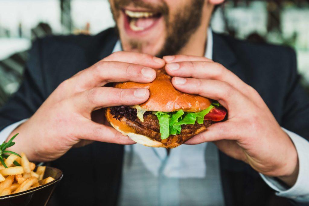 笑顔でハンバーガーを食べている男性