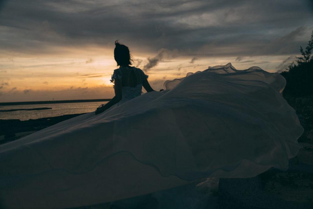 ウェディングドレスを身にまとい夕陽をみている女性