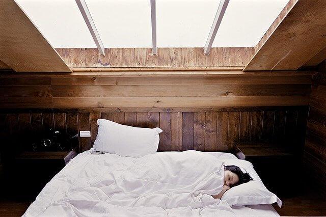 コテージのベッドで眠る女性